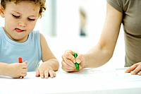 Mother and son coloring with crayons together, boy sticking tongue out, cropped view
