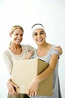 Young female holding cardboard box, mother holding her shoulders