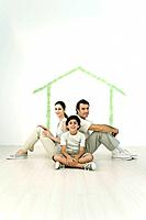 Family sitting back to back in front of outline of house painted on wall (thumbnail)
