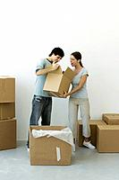 Couple unpacking, man showing contents of one box, woman's mouth open in surprise