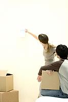 Woman hanging picture frame on wall, man watching, holding cardboard box (thumbnail)