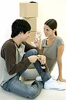 Couple sitting on the floor together, woman holding pair of wine glasses, man opening wine bottle