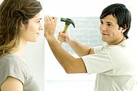 Couple smiling at each other, man hammering nail into wall