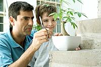 Father and son pruning potted plant together, boy smiling