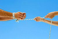 Male hands bound by rope, female hands pulling rope, cropped view