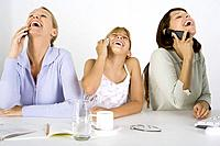 Two women and a preteen girl sitting at table, each using cell phone, all laughing and looking up