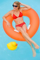 young woman with floating tire in swimming pool