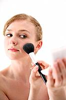 Woman applying blusher on her cheek