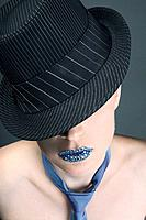 Woman with rhinestones on her lips wearing hat and necktie