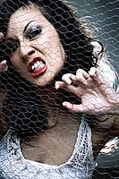 Young woman posing behind wire mesh (thumbnail)