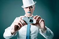 Woman with rhinestones on her lips taking picture with digital camera