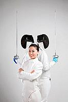 Woman and two men in fencing suits posing for the camera (thumbnail)