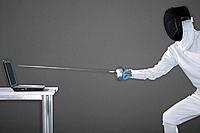 Man in fencing suit aiming fencing foil at a laptop