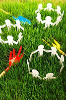 Gardening tools and paper chain dolls on grass