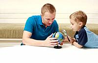 Man turning globe, boy looking at globe through magnifying glass