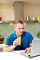 Man holding a glass of orange juice while using laptop