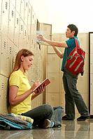 Woman writing some notes while man is keeping his books in the locker