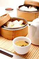 Dim sum in bamboo steamers with a pot of chinese tea