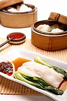 Dim sum in bamboo steamers with a plate of rice noodle roll