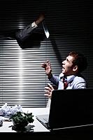Terrified businessman looking at hand with knife coming out from window blinds