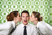 Two businesswomen kissing businessman on cheeks