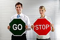 Businessman with a 'Go' sign, businesswoman with a 'Stop' sign
