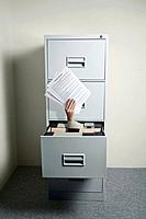 Businesswoman's hand coming out from an opened cabinet holding papers (thumbnail)