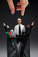 Businessman standing amongst stationery in the pencil holder, giant hand about to pick him up