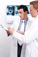 Doctors discussing while looking at papers on clipboard