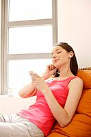 Woman listening to MP3 player with her eyes closed