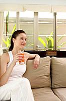 Woman with a glass of fruit juice sitting on the couch