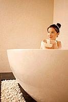 Woman in the bathtub holding bath sponge