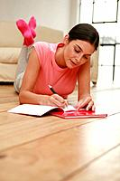 Woman lying forward on the floor writing diary