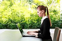 Woman in formal wear using laptop