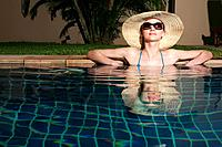 Woman with sunglasses and hat relaxing in the pool