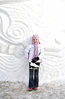 9-year old girl with skates beside snow sculpture, The Forks, Winnipeg, Canada