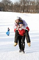 15 year old piggy-backs 13 year old girl up hill, outdoor winter, Winnipeg, Canada