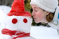Thirteen year old girl offers a kiss to a snowman, Winnipeg, Canada