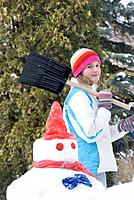 Thirteen year old girl with shovel beside snowmen, Winnipeg, Canada