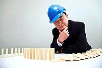 Businessman with safety helmet looking at fallen wooden blocks