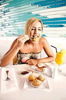 Woman eating fried puff pastry with chopsticks