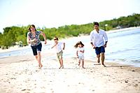 Family of four running along shoreline, Grand Beach Provincial Park, Manitoba, Canada