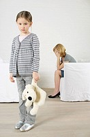 Despaired woman sitting in armchair, girl holding stuffed animal standing in foreground