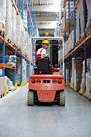 Young man sitting on a fork lift