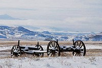 Abandoned wagon parts in snow, Wind River Valley, Wyoming, USA