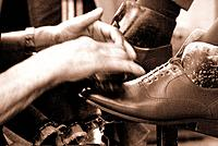 person polishing a pair of shoes