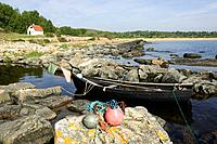 Cliffs and stones and a rowing boat in the sea, Österlen, Skåne, Sweden
