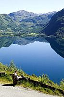 Man reads a book and have a beautiful view over lake and mountains, the Röldals water Röldalsvattnet, Norway