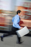 Blurred image of businessman running past a storefront window