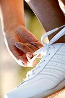 Close up of white sports shoe is seen as one person ties the shoelace